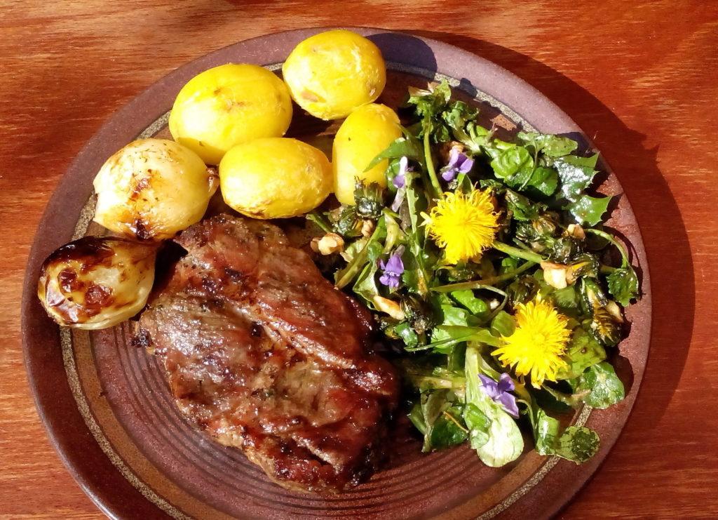 Paleo-Paläo-Essen aus Fleisch Kartoffeln Zwiebeln und Frühlingskräutersalat